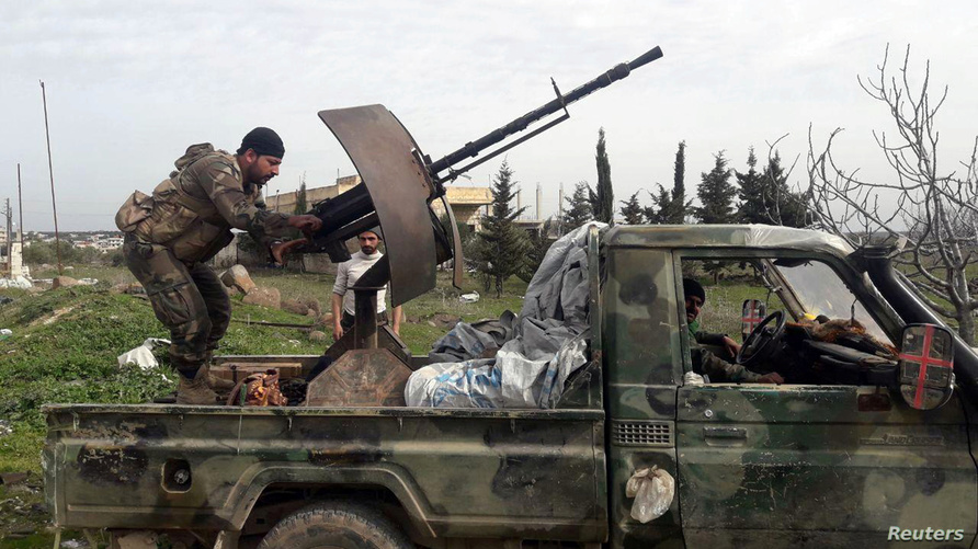 Syrian army soldiers gesture from a military vehicle in southern Idlib province, Syria in this handout released by SANA on…