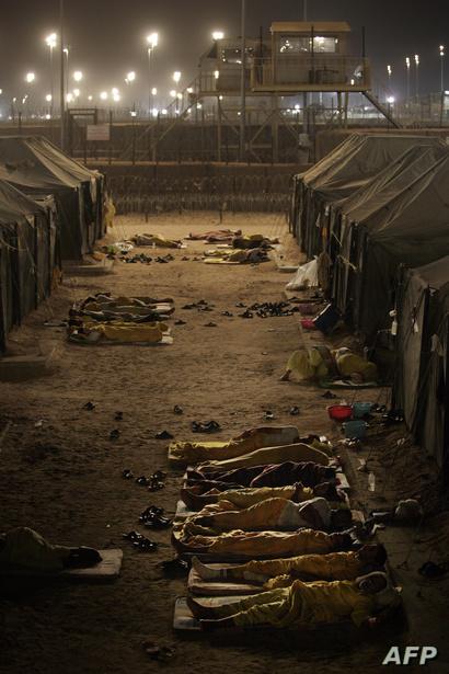 سجناء عراقيون متشددون ينامون خارج خيامهم في سجن بوكا